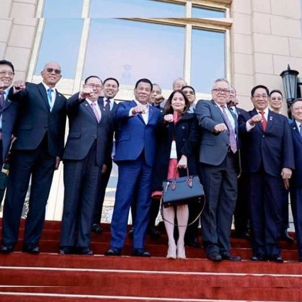President Duterte flashes his signature pose with the members of his delegation following a successful bilateral meeting with Chinese President Xi Jinping at the Great Hall of the People in Beijing on April 25.
