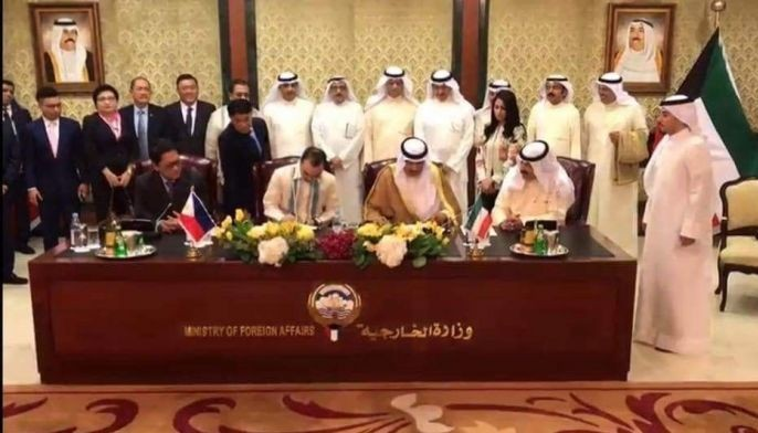 In this May 2018 photo, Philippine and Kuwaiti officials sign a memorandum of understanding for the protection of Filipino domestic workers.
