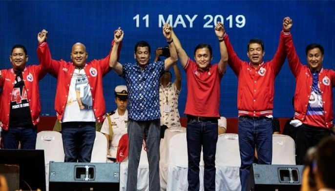 Philippine President Rodrigo Duterte (C) raises the hands of senatorial candidates during the Partido Demokratiko Pilipino-Lakas Bayan (PDP-LABAN) in Manila on May 11, 2019 ahead of the mid-term elections on May 13.