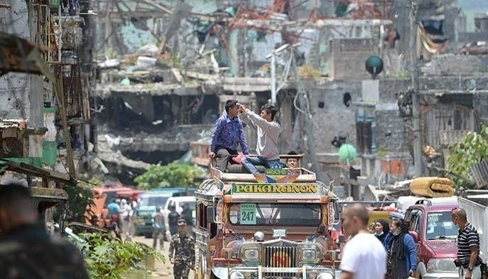 In this April 1, 2018 photo, residents on top of their jeepney take photos of destroyed buildings during a visit to their homes at the main battle area in Marawi City. The US Department of State has issued travel advisory Level 4 for the war-torn city due to the threat of civil unrest and terrorism.
