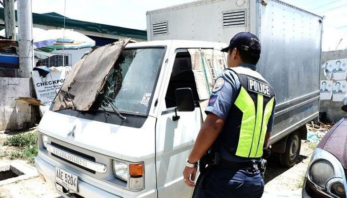 A policeman checks on the L300 van owned by Chinese national Yi Feng Guo Yang, 51 years old, who was shot dead by unidentified perpetrators in Barangay Cubacub, Mandaue City on Monday night. Yi's two children were wounded but survived the attack.