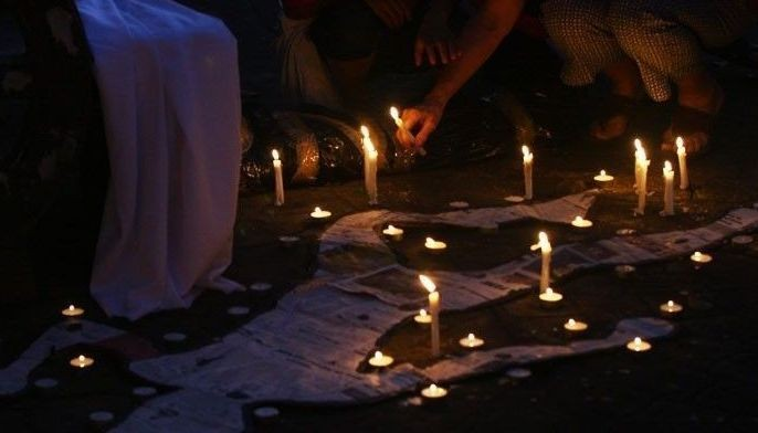 File photo shows people lighting candles to protest drug war killings.