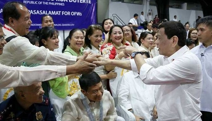 """President Rodrigo Duterte shares a light moment with the guests during the """"Araw ng Pasasalamat"""" for the Overseas Filipino Workers (OFWs) at Camp General Emilio Aguinaldo in Quezon City on July 12, 2019."""