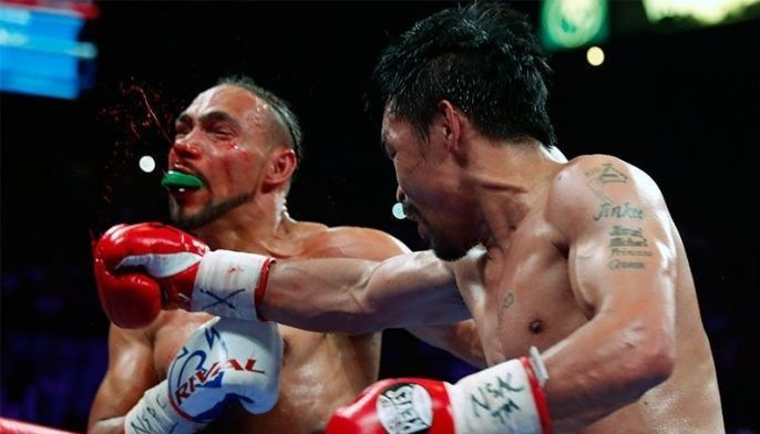 Keith Thurman (L) takes a punch from Manny Pacquiao during their WBA welterweight title fight at the MGM Grand Garden Arena on July 20, 2019 in Las Vegas, Nevada.