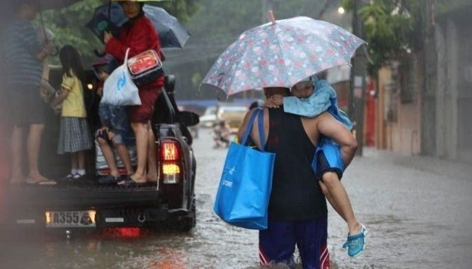 In this Aug. 11, 2018 photo, school children are being evacuated after being trapped due to the waist-deep flood at Twin River in Barangay Parang, Marikina City.