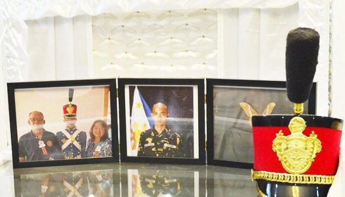 Photos of PMA cadet Darwin Dormitorio and his cap are displayed on top of his coffin at the Cosmopolitan Funeral Home in Cagayan de Oro.