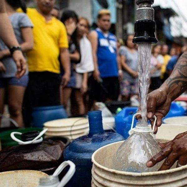 Residents of Addition Hills in Mandaluyong City, Manila, queue to receive water distributed on water tank truck and fire trucks on March 15, 2019.