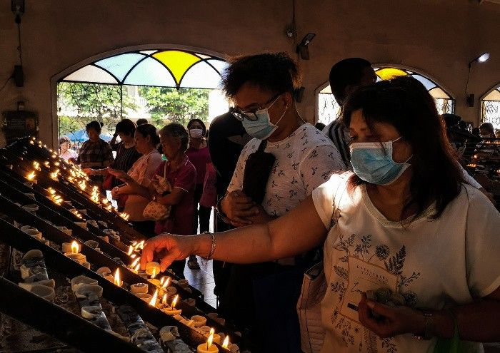Filipino Catholics wearing masks to protect against COVID-19
