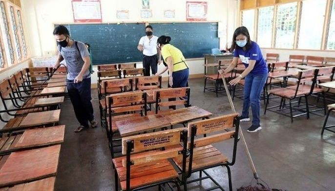 FILE - In this March 9, 2020 photo, school workers disinfect a classroom amid the novel coronavirus threat in the country.